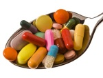 Many different tablets and medicines are on a spoon